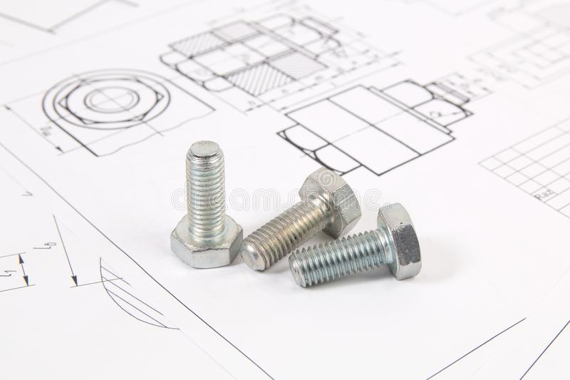 Technical drawings of bolts. Engineering, technology and metalworking. Metal bolt on printed drawings background stock photo