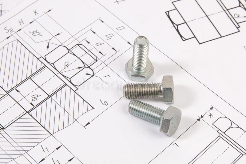 Technical drawings of bolts. Engineering, technology and metalworking. Metal bolt on printed drawings background royalty free stock images