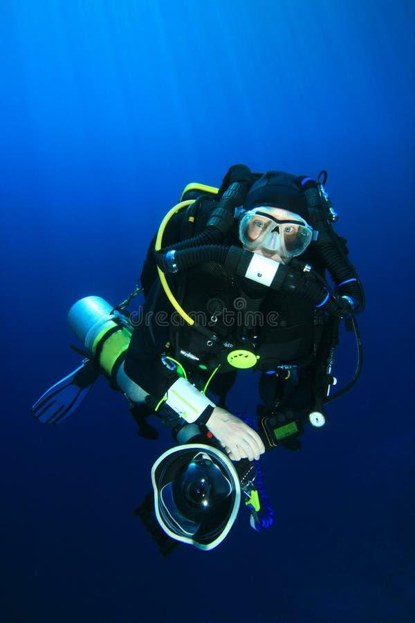 Technical Scuba Diver. A deep explorer technical diver wearing a Closed-Circuit Rebreather, carrying a SLR camera stock photos