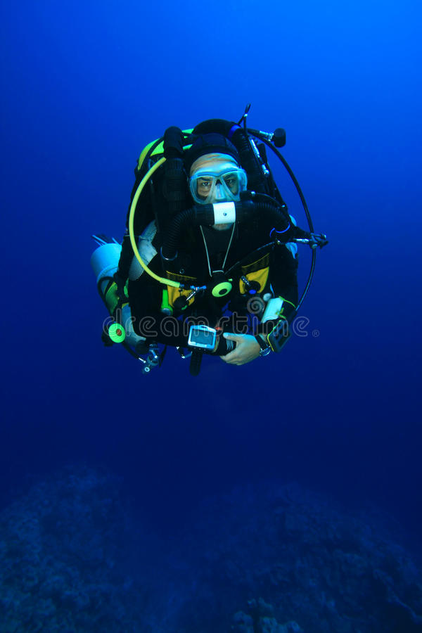 Technical Scuba Diver. A deep explorer technical diver wearing a Closed-Circuit Rebreather, carrying a SLR camera stock photo