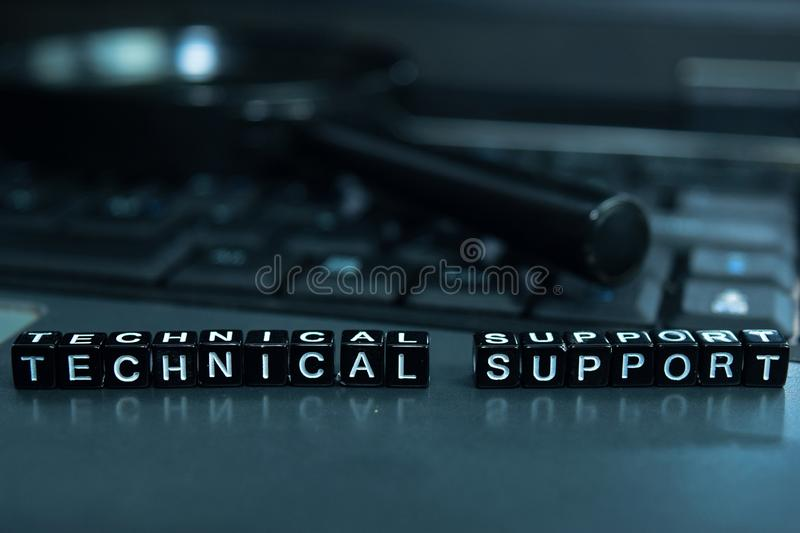 Technical Support text wooden blocks in laptop background. Business and technology concept stock images