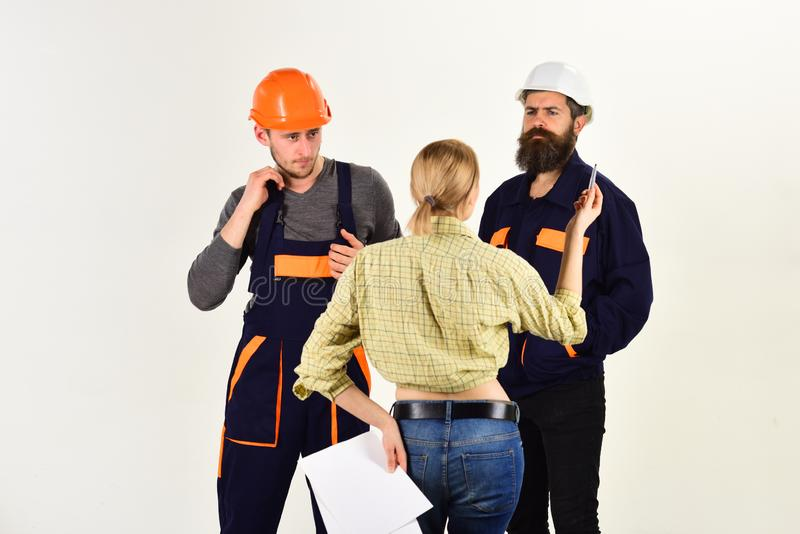 Technical task concept. Brigade of workers, builders in helmets, repairers and lady customer discussing contract, white royalty free stock image