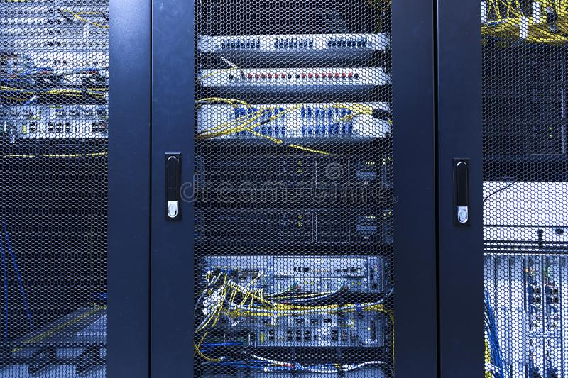 Technical wall of cellular data terminal in modern communication center. Close up backhaul network equipment under closed meshed. Technical wall of cellular data royalty free stock photography
