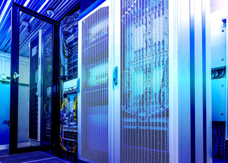 Technical wall of cellular data terminal rows with opened mesh door. modern data center blue toning. Technical wall of cellular data terminal rows with opened royalty free stock image