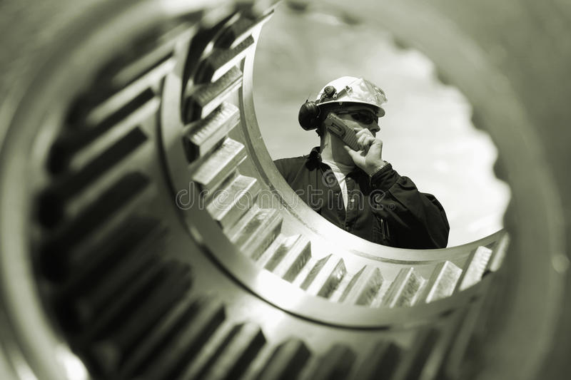 Technical worker and large gears shafts. Worker, engineer seen through a large gears shaft royalty free stock photo
