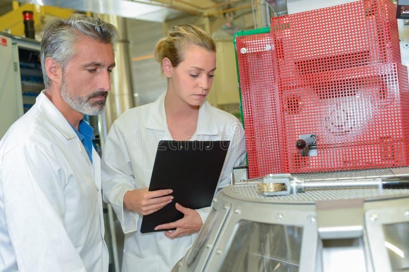 Technicans runt om industriell utrustning arkivbild