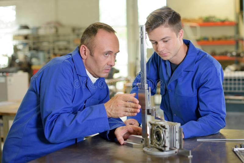 Technician and apprentice setting up equipment stock image