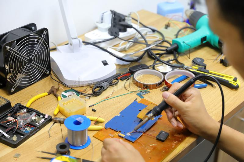 Technician bonding two wires with a solder joint. royalty free stock photography