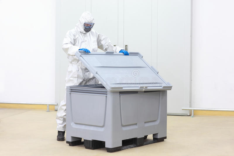 Technician checking contents of containrt. Fully protected technician lifting cover of plastic container checking contents royalty free stock photos