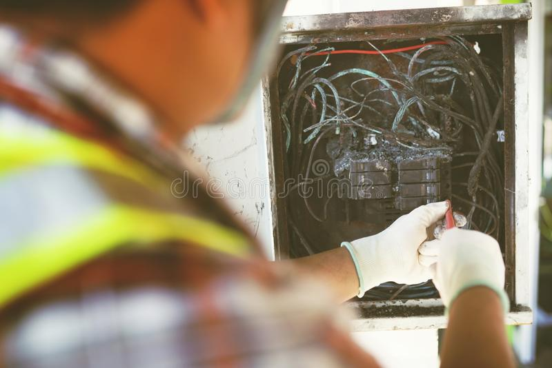 Technician checking electrical switch board on fire short circuit royalty free stock image