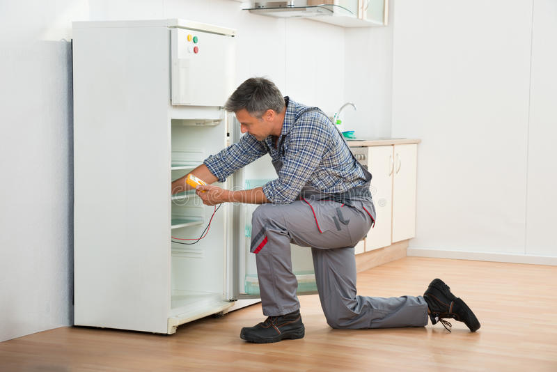 Technician Checking Fridge With Digital Multimeter royalty free stock image