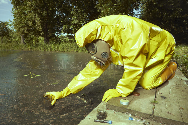 Technician in chemical protective suit collecting water contamination samples. Man in chemical protective suit collecting samples of water contamination stock photos