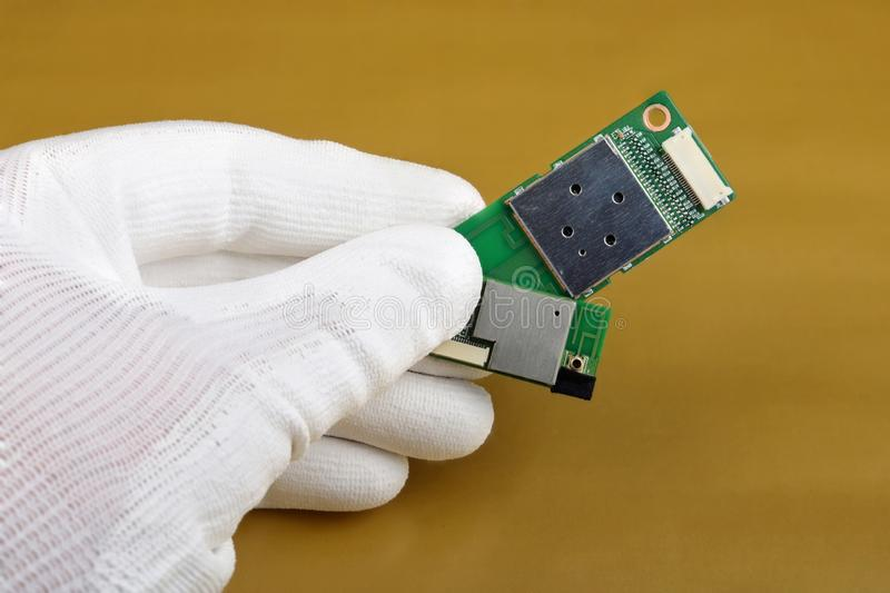 A technician controls the quality of a mini wifi modules for mobile devices royalty free stock images
