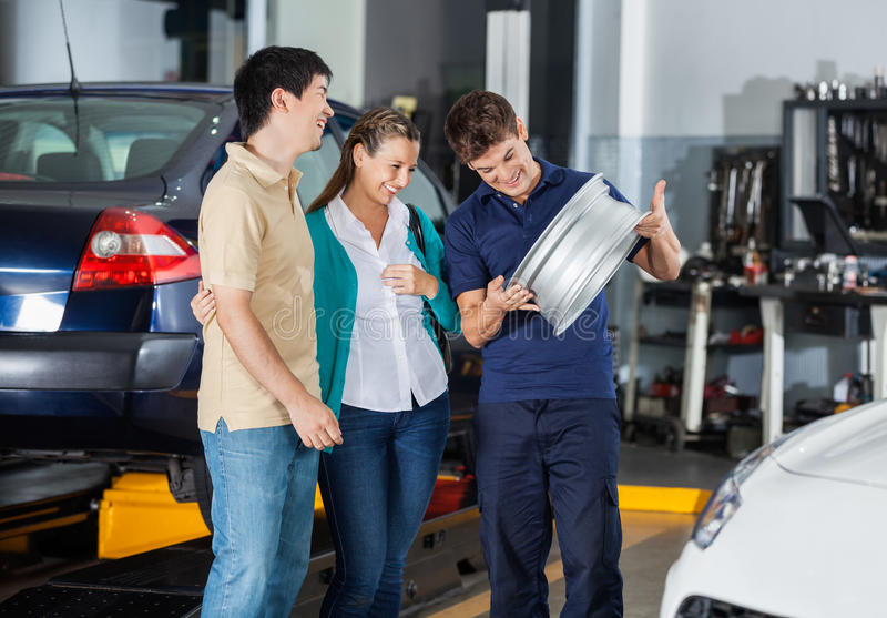 Technician And Couple Looking At Hubcap. Happy male technician and couple looking at metallic hubcap in garage royalty free stock images