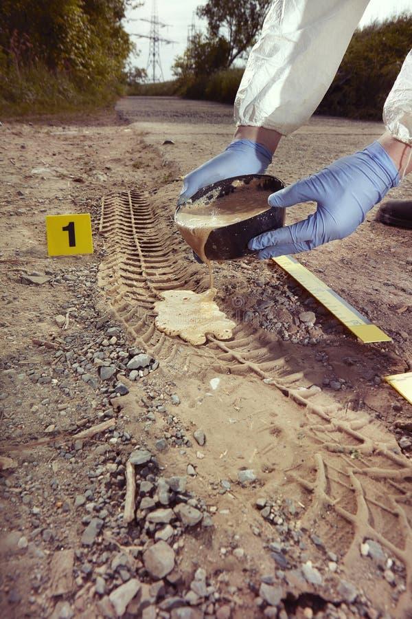 Technician Criminologist preparing tire print left in dust of field way for documentation. Crime scene investigation - casting of car tire print left on crime stock photos
