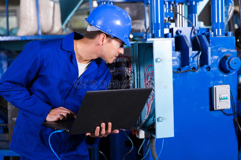 Technician distribution box. Industrial technician checking distribution box with laptop in factory stock images