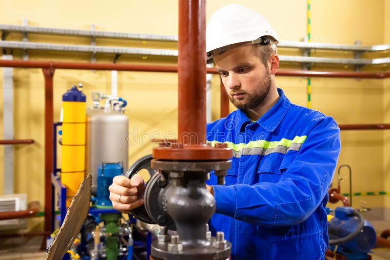 Technician employee opens gate valve on industrial pipeline. Services works on gas and oil station. Maintenance pumps and boiler on gas factory stock images