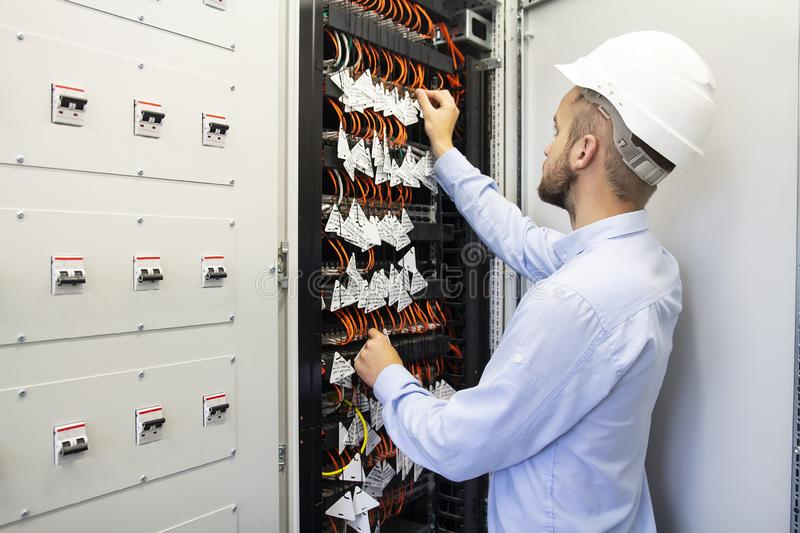 Technician engineer in datacenter. Network technician connecting fiber optic at server room. royalty free stock image