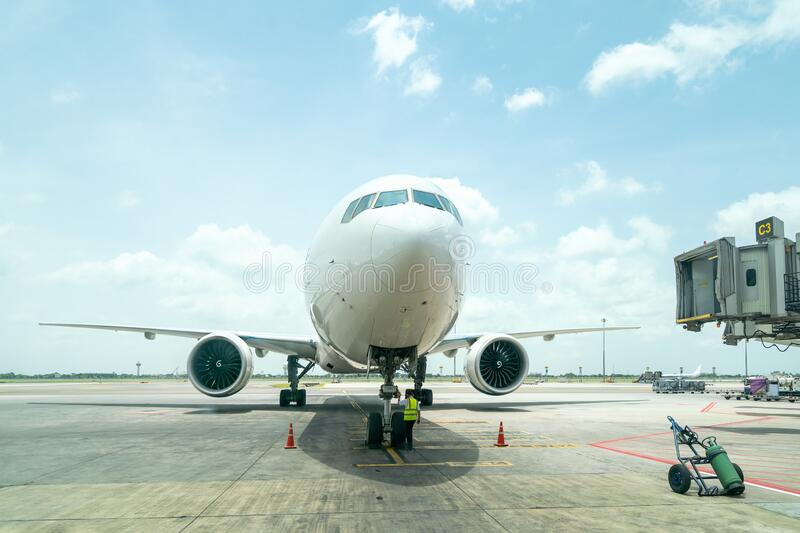 Technician or engineer safety check of modern passenger or cargo airplane parking at terminal gate of international airport on a royalty free stock photos