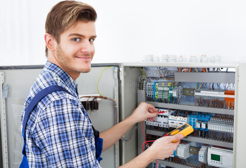 Technician examining fusebox with insulation resistance tester royalty free stock image