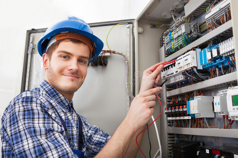 Technician examining fusebox with multimeter probe. Side view of male technician examining fusebox with multimeter probe royalty free stock photo