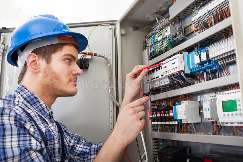Technician examining fusebox with multimeter probe. Side view of male technician examining fusebox with multimeter probe royalty free stock images