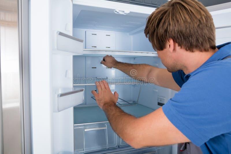 Technician Examining Refrigerator stock images