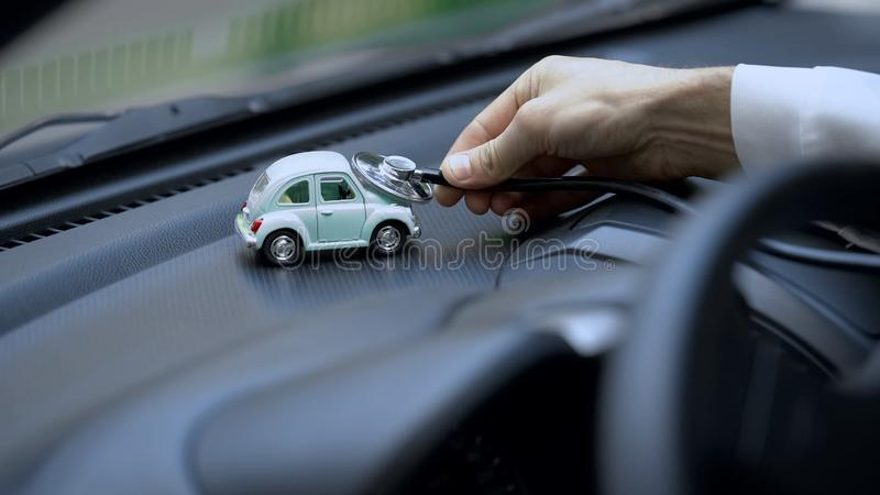 Technician examining toy car with stethoscope, vehicle insurance, maintenance royalty free stock photo