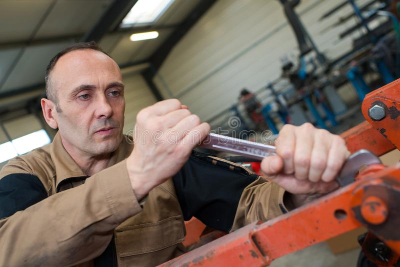 Technician in factory at machine maintenance working with wrench. Man stock image