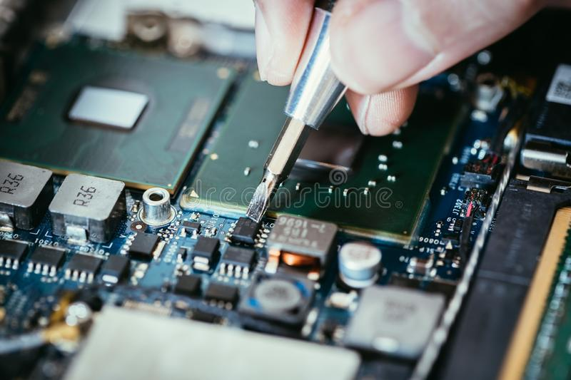 Technician is fixing a computer circuit board, hand and screwdriver. Computer circuit board, hand and screwdriver: Technician is fixing a motherboard chip stock photo