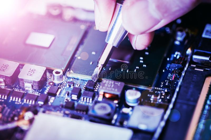 Technician is fixing a computer circuit board, hand and screwdriver. Computer circuit board, hand and screwdriver: Technician is fixing a motherboard chip stock images
