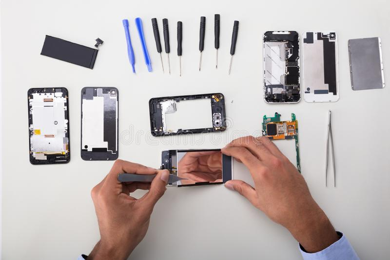 Technician Fixing Damaged Screen On Mobile Phone stock photo