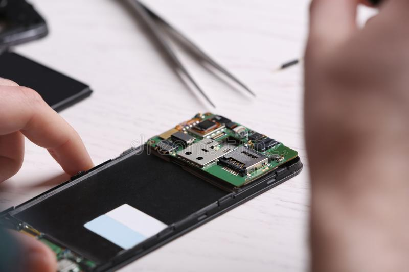 Technician fixing mobile phone at table. Device repair service stock images