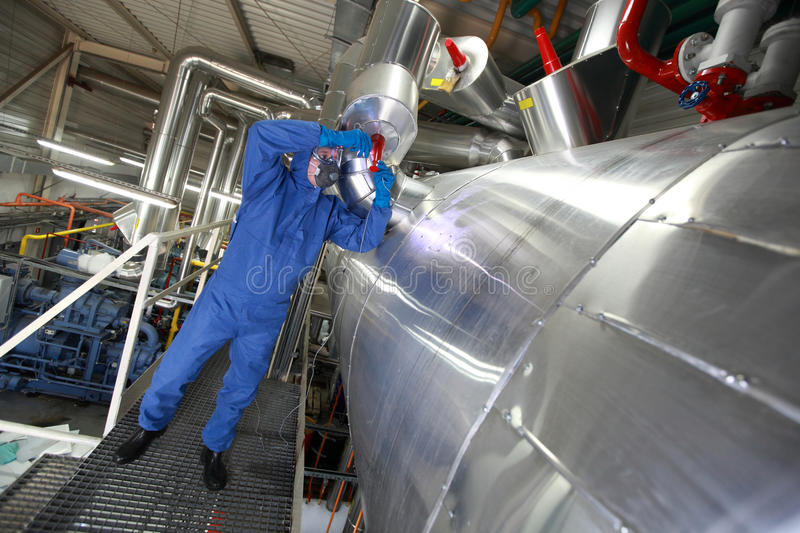 Technician fixing technological system. Technician in mask,gloves,goggles and blue uniform reparing technological system stock images