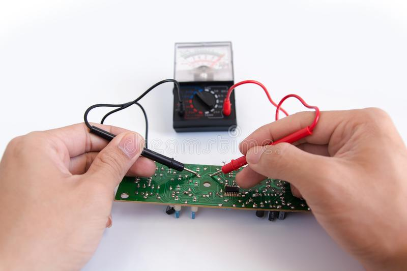 Technician hand with multimeter probes repairing circuit board royalty free stock photo