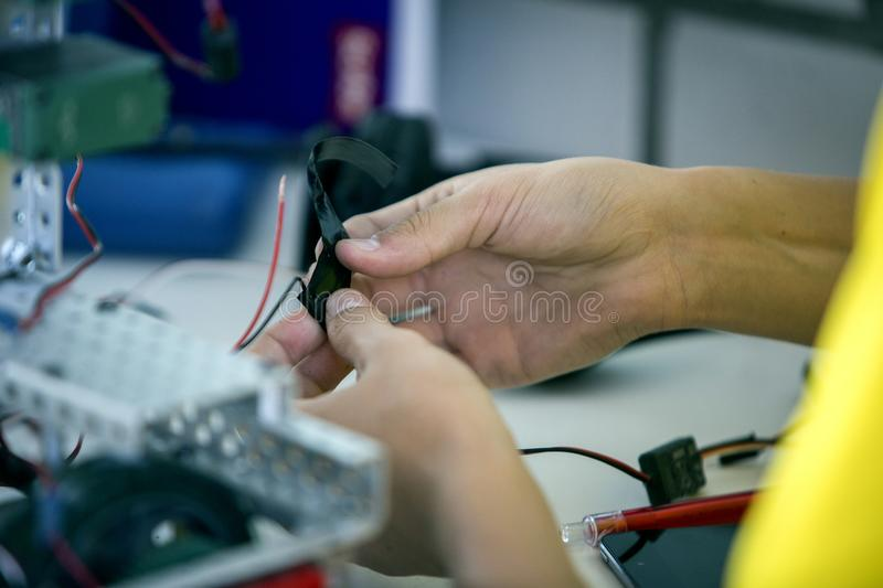 Technician hands. Hands of technician putting cables in workshop stock photos