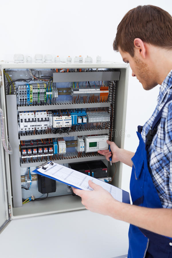 Technician holding clipboard while examining fusebox stock images