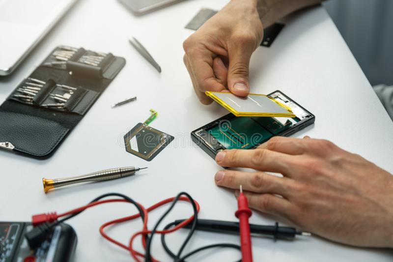 Technician installing new battery in phone stock image
