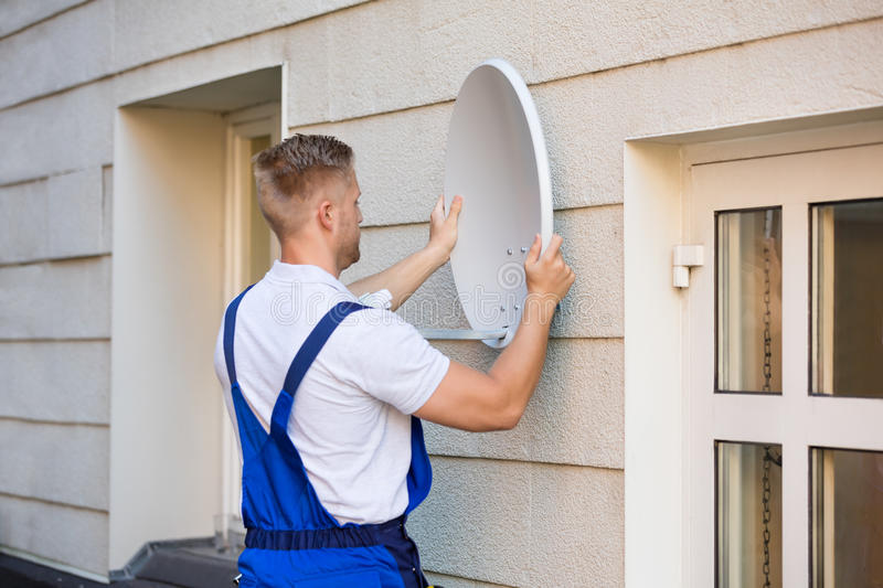 Technician Installing TV Satellite Dish. Young Male Technician Installing TV Satellite Dish To Wall royalty free stock photo