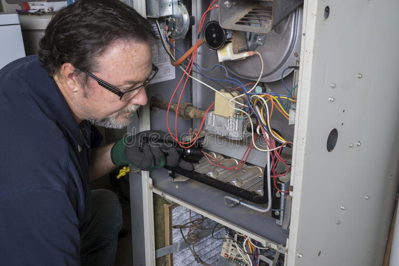Technician Looking Over A Gas Furnace royalty free stock photo