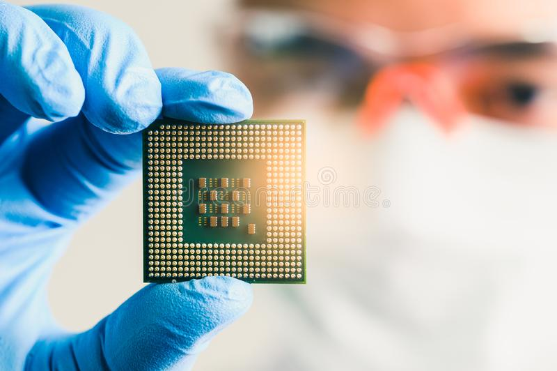 The technician looking to the CPU for analyzing in the lab. the concept of computer, service, electronics, hardware, repairing, up royalty free stock photo