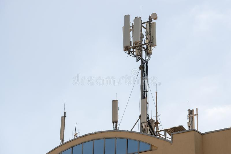 Technician maintenance on telecommunication tower doing ordinary maintenance control to an antenna for communication 3G 4G and 5G. Description: Technician stock photos