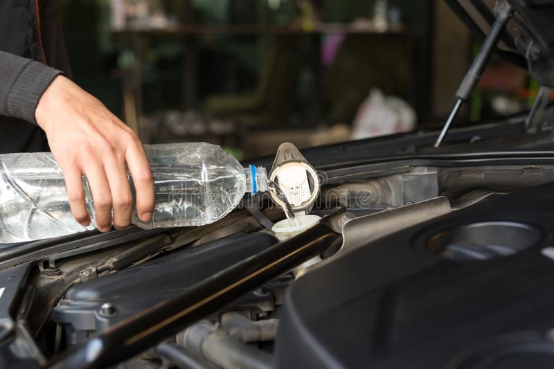 Man pouring water into car windshield water tank stock photography