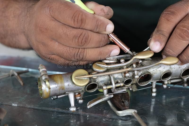 The technician man is repairing the vintage style saxophone instrument. The technician man is repairing the vintage style saxophone instrument stock photo