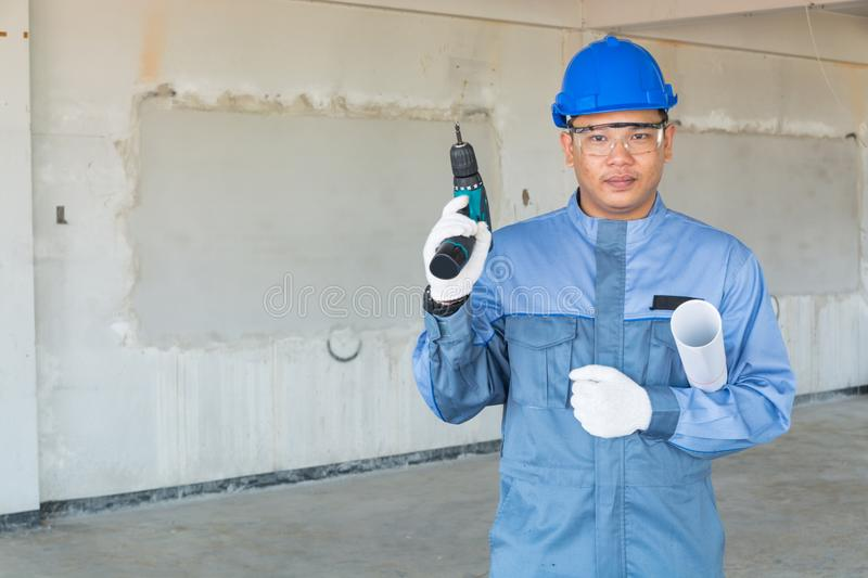 Technician or Mechanic wear Blue Hardhat and Protection Suit hold Drill and Blueprint ready to Serve Customer as Home Maintenance stock photography