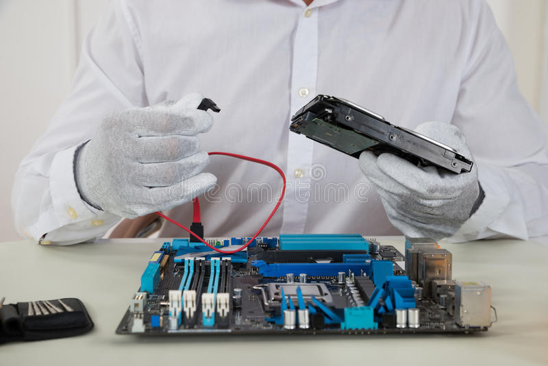 Technician With Motherboard And Harddisk. Close-up Of Male Technician With Motherboard And Harddisk royalty free stock photo