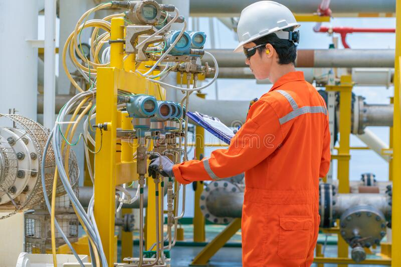 Technician operator checking and record reading value of pressure, temperature and flow transmitter in daily log book at offshore. Oil and gas central royalty free stock image