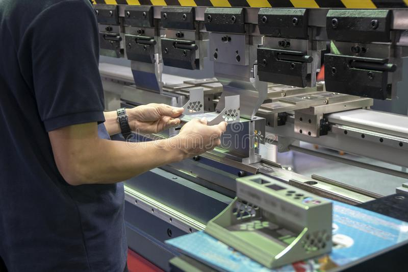 The technician operator use hydraulic bending machine. The sheet metal manufacturing process stock image