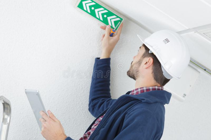 Technician placing emergency exit sign stock photos