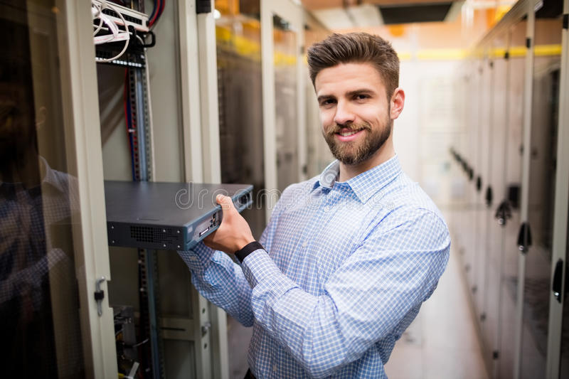 Technician removing server from rack mounted server. Portrait of technician removing server from rack mounted server in server room stock image